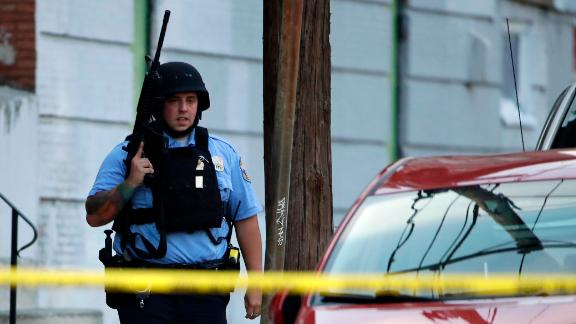 A police officer patrols the block near the shooting scene in Philadelphia on Wednesday.