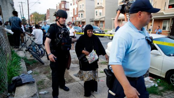 Police officers escort a bystander away from the scene of the shooting in Philadelphia on Wednesday.