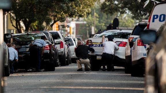 Police officers take cover behind parked cars.