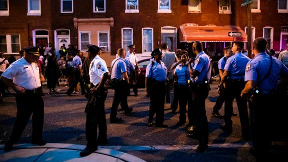 Officers gather for crowd control near a massive police presence set up outside a house as they investigate an active shooting situation, in Philadelphia, Wednesday, Aug. 14, 2019. (AP Photo/Matt Rourke)