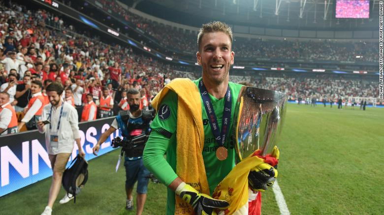 Liverpool's Adrián celebrates with the UEFA Super Cup trophy.