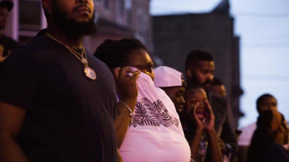 A bystander wipes her eyes after she was pepper-sprayed by police.
