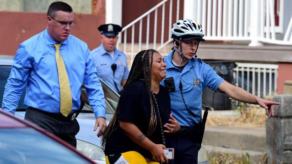 Police escort an unidentified bystander away from the scene.