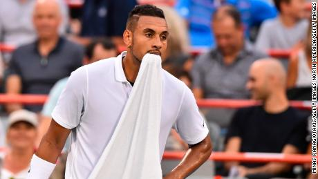 Nick Kyrgios holds his towel in his mouth after losing against Britain's Kyle Edmund in August.