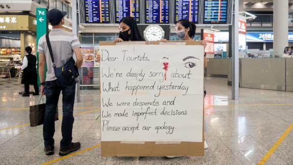 Demonstrators hold a sign at the Hong Kong International Airport in Hong Kong, China, on Wednesday, Aug. 14, 2019.