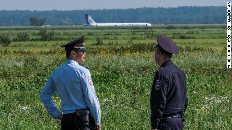 Police officers stand guard near the site of hard landing of the Ural Airlines A321 plane on a corn field near Moscow's Zhukovsky airport on August 15, 2019. - A Russian pilot was being hailed as a hero on August 15, 2019 for landing an Airbus carrying more than 230 people in a Moscow corn field after a bird strike. (Photo by Yuri KADOBNOV / AFP)        (Photo credit should read YURI KADOBNOV/AFP/Getty Images)