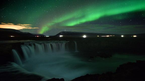 The northern lights appear over a waterfall in Iceland.