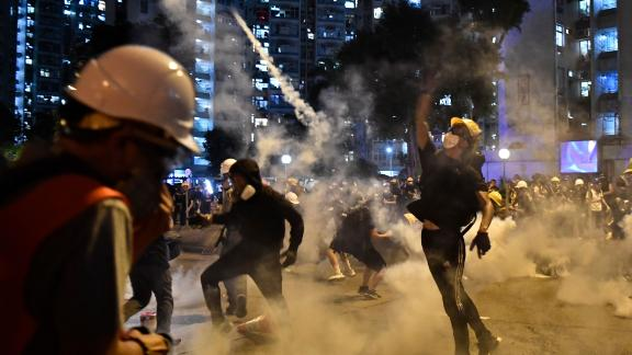 Protesters throw back tear gas fired by the police in Wong Tai Sin during a general strike in Hong Kong on August 5, 2019.