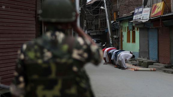 An Indian soldier stands guard as Kashmiri Muslims offer Friday prayers outside a Srinagar mosque on August 16.