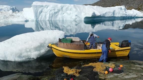 ILULISSAT, GREENLAND - JULY 30: Inuit fishermen prepare a net as free-floating ice floats behind at the mouth of the Ilulissat Icefjord during unseasonably warm weather on July 30, 2019 near Ilulissat, Greenland. The Sahara heat wave that recently sent temperatures to record levels in parts of Europe is arriving in Greenland. Climate change is having a profound effect in Greenland, where over the last several decades summers have become longer and the rate that glaciers and the Greenland ice cap are retreating has accelerated.   (Photo by Sean Gallup/Getty Images)