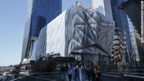 People walk by the new arts center The Shed on the Hudson Yards on April 03, 2019 in New York City. - The Sheds is a movable structure and will be the arts center designed exclusively to commission, produce, and present all types of performing arts, visual arts, and popular culture. (Photo by Kena Betancur / AFP)        (Photo credit should read KENA BETANCUR/AFP/Getty Images)