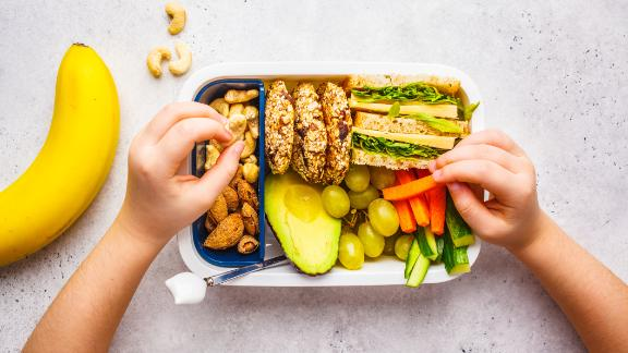 School healthy lunch box with sandwich, cookies, nuts, fruits and avocado on a white background.