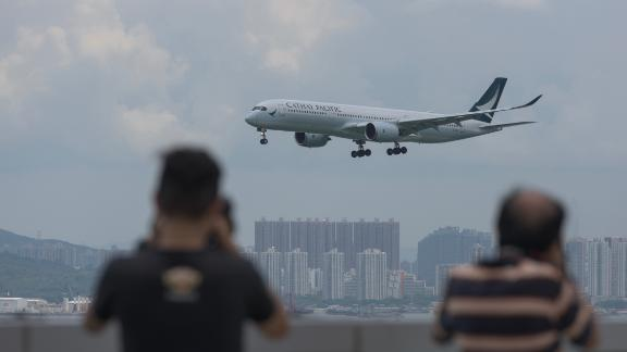 A Cathay Pacific passenger plane makes its descent before landing at Hong Kong