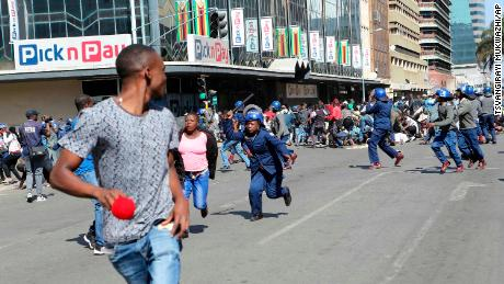 People run away from riot police armed with batons during clashes in Zimbabwe's capital on Friday.