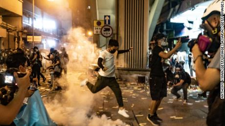 A protester attempts to kick a tear gas canister during a demonstration on Hungry Ghost Festival day in Sham Shui Po district on August 14, 2019 in Hong Kong.