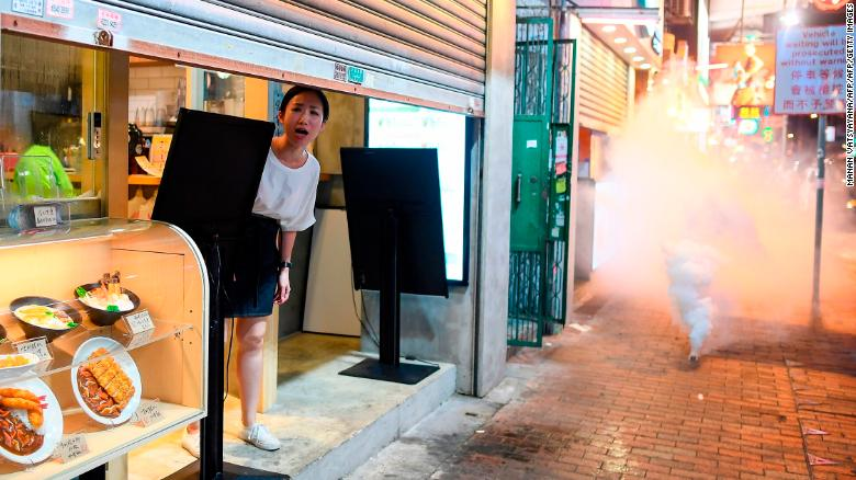 A woman reacts as police personnel fire tear-gas shells to disperse pro-democracy protestors in the Sham Shui Po Area of Hong Kong on August 14, 2019.