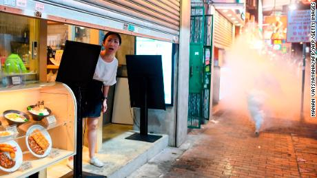 Woman reacts as police personnel to tear gas by a tear gas gun against democracy in the Sham Shui Po area of Hong Kong on August 14, 2019.