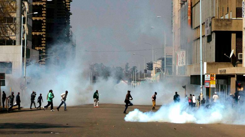 Protesters run from teargas fired by riot police during protests in Harare on Friday.
