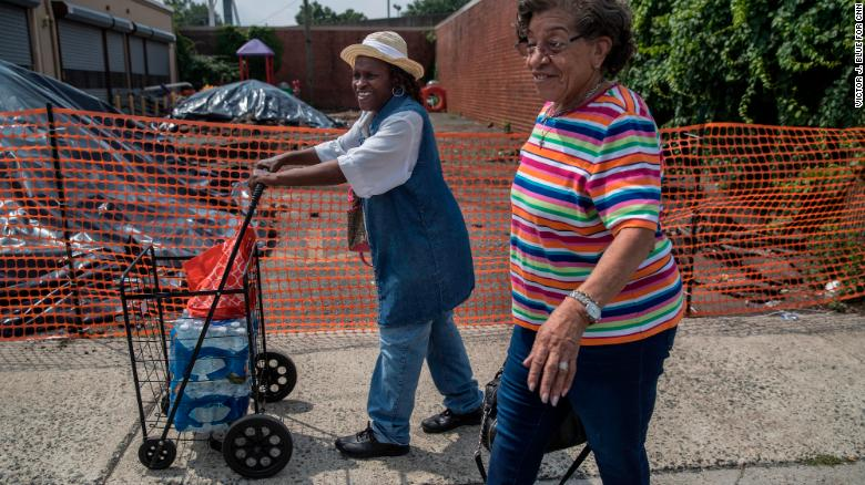 Lorraine Macklin, left, and Edith Tappins pick up bottled water in Newark.