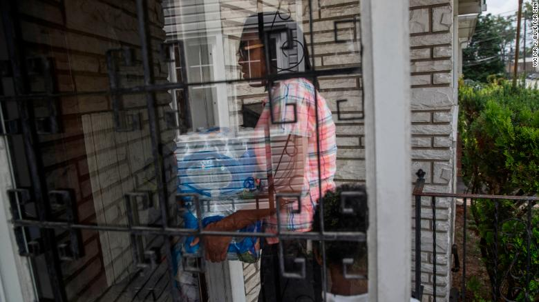 Shakima Thomas carries bottled water into her home.