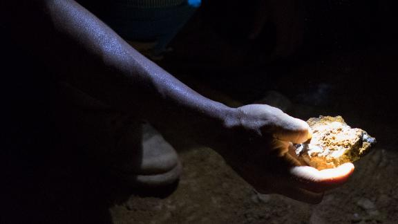 Miner holds a piece of rock, deep inside a mine in Venezuela