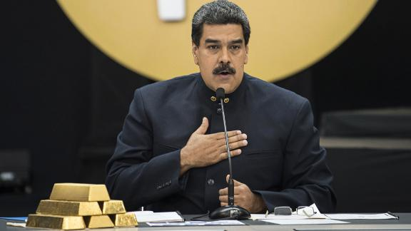 Nicolas Maduro speaks next to a stack of gold ingots during a news conference on the country