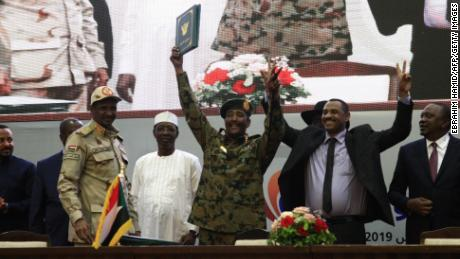 "Sudan's protest leader Ahmad Rabie (2nd-R), flashes the victory gesture alongside General Abdel Fattah al-Burhan (C), the chief of Sudan's ruling Transitional Military Council (TMC), during a ceremony where they signed a ""constitutional declaration"" that paves the way for a transition to civilian rule, in the capital Khartoum on August 17, 2019, accompanied by General Mohamed Hamdan Daglo ""Hemeti"" (2nd-L), TMC deputy chief and commander of the Rapid Support Forces (RSF) paramilitaries, Ethiopian Prime Minister Abiy Ahmed (L), South Sudan President Salva Kiir Mayardit (2nd-R, behind), Chadian President Idriss Deby (3rd-L), and Kenyan President Uhuru Kenyatta (R). - The agreement was signed by Mohamed Hamdan Daglo, deputy chief of the military council, and Ahmed al-Rabie, representing the Alliance for Freedom and Change protest umbrella group, an AFP reporter said. Heads of state, prime ministers and dignitaries from several countries attended the ceremony in Khartoum. (Photo by Ebrahim HAMID / AFP)        (Photo credit should read EBRAHIM HAMID/AFP/Getty Images)"