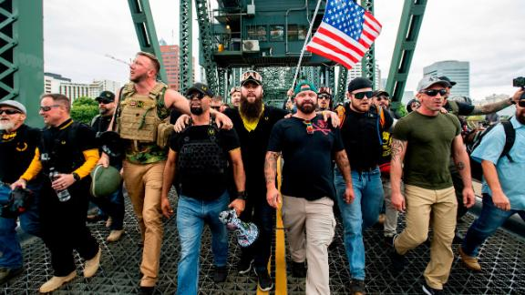 """Members of the Proud Boys and other right-wing demonstrators march across the Hawthorne Bridge during an """"End Domestic Terrorism"""" rally in Portland, Ore., on Saturday, Aug. 17, 2019. The group includes organizer Joe Biggs, in green hat, and Proud Boys Chairman Enrique Tarrio, holding megaphone. (AP Photo/Noah Berger)"""