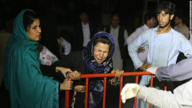 A woman grieves at the door of the hospital, after a blast hit a wedding ceremony in Kabul, Afghanistan.