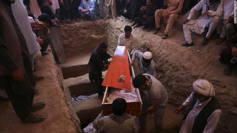 Afghans carry the body of a victim of a wedding hall bombing during a mass funeral in Kabul.