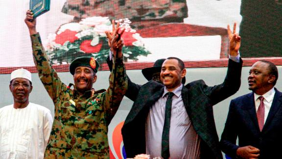 Sudanese protest leader Ahmad Rabie, center right, flashes the victory gesture alongside Gen. Abdel Fattah al-Burhan, the chief of Sudan's ruling Transitional Military Council, center left, during a ceremony where they signed a constitutional declaration.