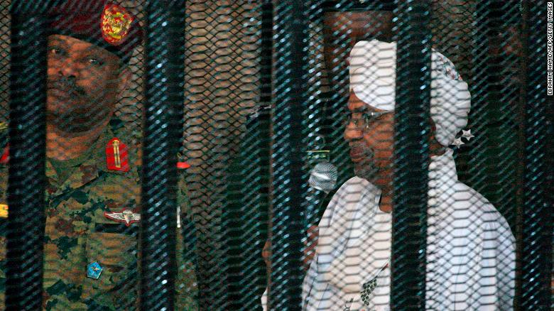 Bashir stands in a defendant's cage on the first day of his trial.