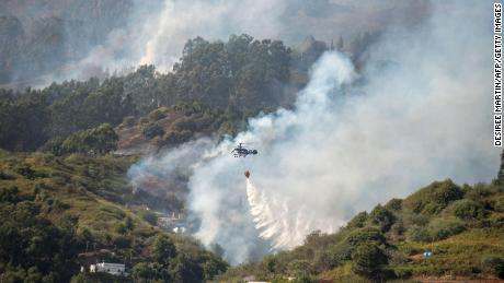 A helicopter drops water on 19 August 2019 during a forest fire in the Moya Mountains on the island of Gran Canaria.