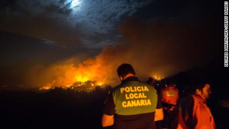 Firemen and policeman watch from the road as a blaze rages in Spain's Canary Islands on August 17, 2019.