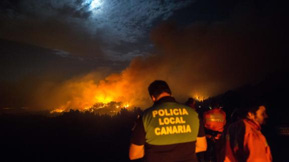 Firemen and policeman watch from the road as a blaze rages in Spain