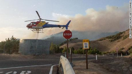 A helicopter of a fire department picks up water before dropping it over a forest fire in Galdar on the island of Gran Canaria on 18 August 2019.