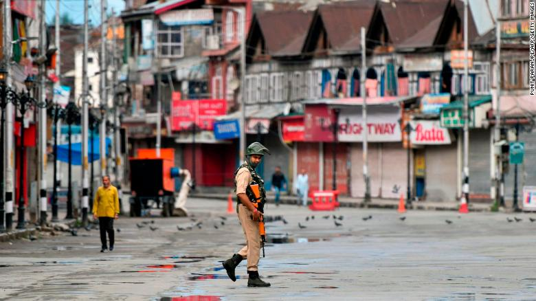 A security personnel patrols on a deserted road of the Lal Chowk area in Srinagar on August 19, 2019.