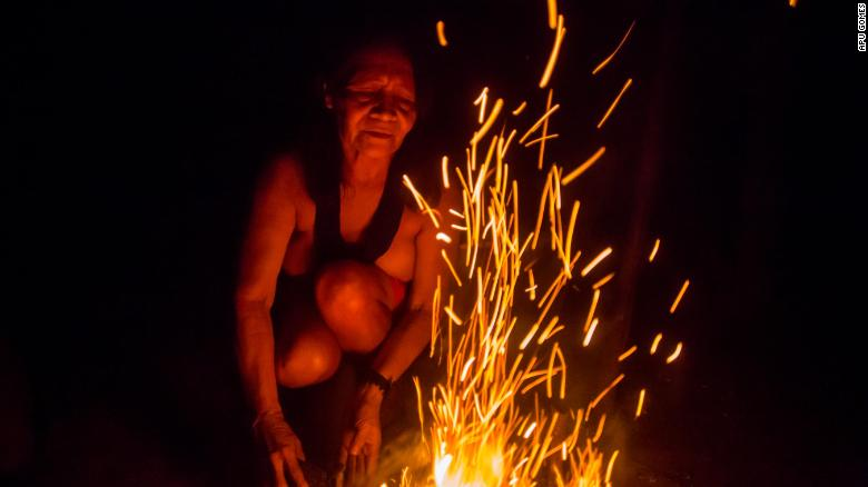 Chief Ajareaty Waiapi builds a bonfire outside her home in Kwapo'ywyry village.
