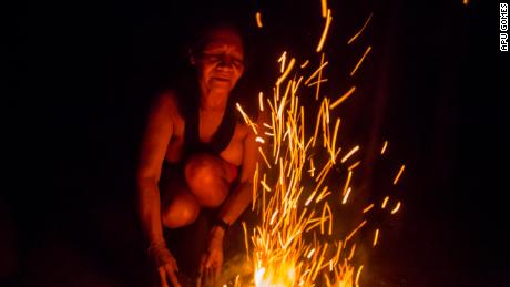 Chief Ajareaty Waiapi builds a bonfire outside her home in Kwapo'ywyry village. She's been working on finding ways to communicate with non-indigenous Brazilians, including studying Portuguese in a local school. The Waiapi fear great fires and floods may destroy the planet if they don't fight to protect the rainforest.
