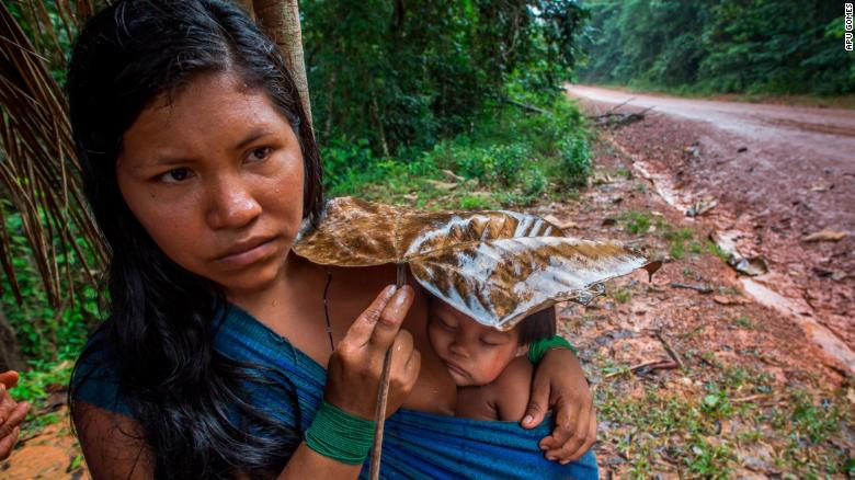 Karuwaniru Waiaipi protects her infant son from the rain with a leaf, as she walks by the BR-210 Perimetral Norte highway near the village of Aramira.
