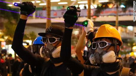 Protesters use laser pointers beam at policemen during the anti-extradition bill protest in Hong Kong, Sunday, Aug. 11, 2019. Police fired tear gas late Sunday afternoon to try to disperse a demonstration in Hong Kong as protesters took over streets in two parts of the Asian financial capital, blocking traffic and setting up another night of likely showdowns with riot police. (AP Photo/Vincent Thian)