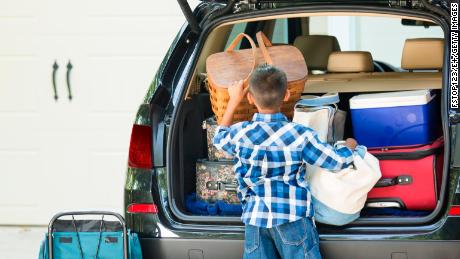 Family packs their vehicle for summer vacation.  One excited little boy waits by the car.