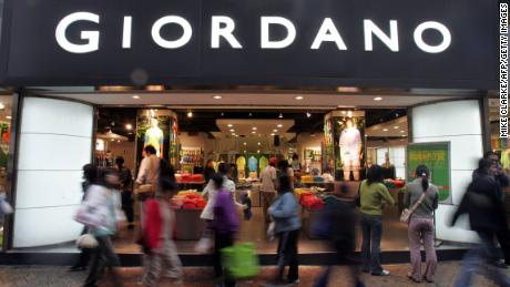 On a rainy day in Hong Kong, March 22, 2005, buyers are passing through a Giordano retail store.