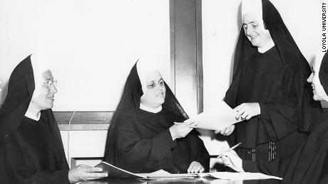 Sister Jean (second from right) looks over paperwork in a vintage photo of her.