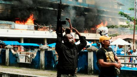 A police officer raises his rifle as the local market is seen burning during a protest in Fakfak in Indonesia's Papua province on Wednesday