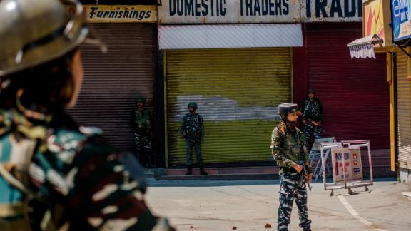 SRINAGAR, KASHMIR, INDIA - AUGUST 20: Indian paramilitary troopers stand guard in front the shuttered shops in the deserted city center, on August 20, 2019 in Srinagar, the summer capital of Indian administered Kashmir, India.  Curfew like restrictions remain in place in Kashmir for the fourteenth consecutive day after India revoked articles 370 and 35A, and phone and internet services also remained suspended. Article 35A of the Indian Constitution was an article that empowered the Jammu and Kashmir state
