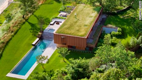 The green roof on this home in Hampton Bays gives the illusion that it has been tucked  into the surrounding meadow.