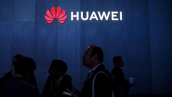 Attendees walk past signage displayed outside the Huawei Technologies Co. booth at the 2019 Consumer Electronics Show (CES) in Las Vegas, Nevada, U.S., on Wednesday, Jan. 9, 2019. Dozens of companies will give presentations at the event, where attendance is expected to top 180,000, with the trade war between the U.S. and China as well as Apple