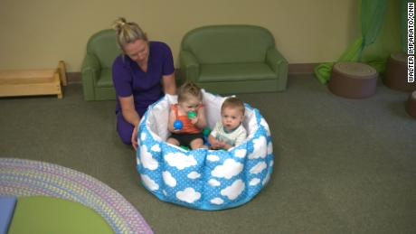 A daycare teacher cares for 11-month old twins. [196909023] A daycare teacher cares for 11-month old twins.