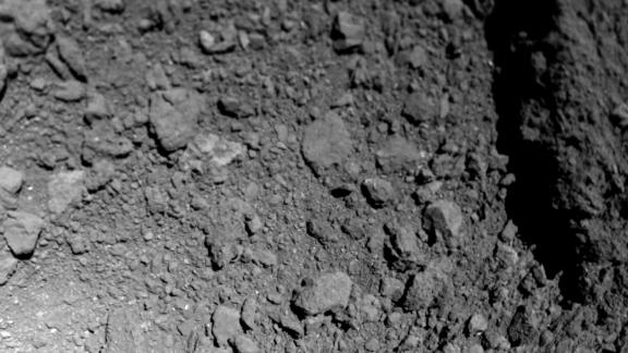 The second image of the DLR-developed MASCAM camera is directed obliquely downward on the asteroid Ryugu and covers areas east of the descent route. Compared with the first image, it is clear that MASCOT moved turbulently towards Ryugu, as expected, thus performing turns and rollovers. The images show a huge boulder, which occupies the eastern (right) edge of the image and is several tens of meters in length. On the bottom left is MASCOT's shadow, which the Sun behind the landing probe is projecting onto the asteroid surface: MASCOT is 30 centimeters long. Ryugu is a body with no atmosphere, so the outlines of MASCOT are sharp in the shadows projected onto the asteroid surface.